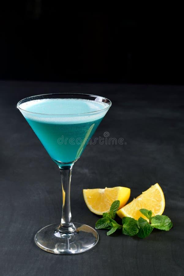 Μπλε κρύο κοκτέιλ martini στο γυαλί με το σκοτεινό υπόβαθρο μεντών λεμονιών στοκ φωτογραφίες με δικαίωμα ελεύθερης χρήσης