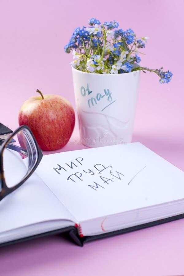 Μπλε λουλούδια άνοιξη σε ένα άσπρο γυαλί Ρόδινη ανασκόπηση τοποθετήστε το κείμενο βιβλία και ένα μήλο Κάρτα Κάθετη φωτογραφία διά στοκ φωτογραφία με δικαίωμα ελεύθερης χρήσης