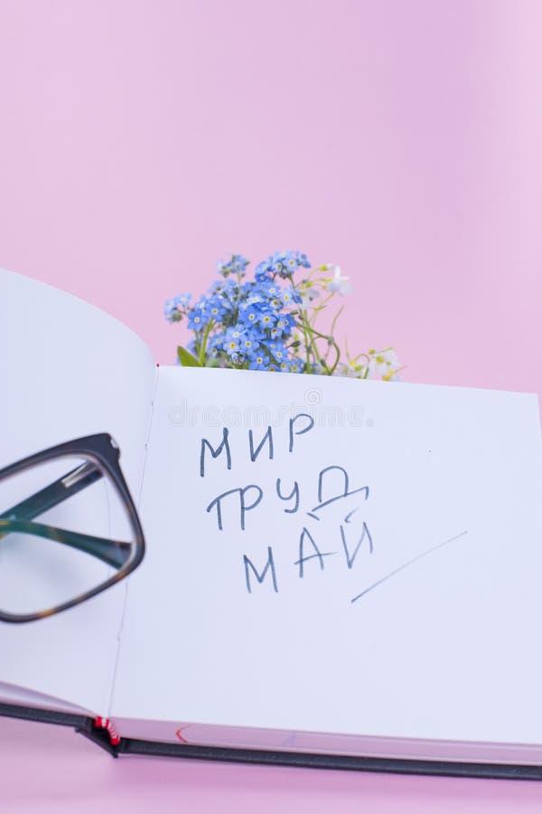 Μπλε λουλούδια και βιβλία και ένα μήλο Γυαλιά και ένα ανοικτό σημειωματάριο Εργασιακή ατμόσφαιρα Διακοπές της εργασίας το Μάιο κε στοκ φωτογραφία με δικαίωμα ελεύθερης χρήσης