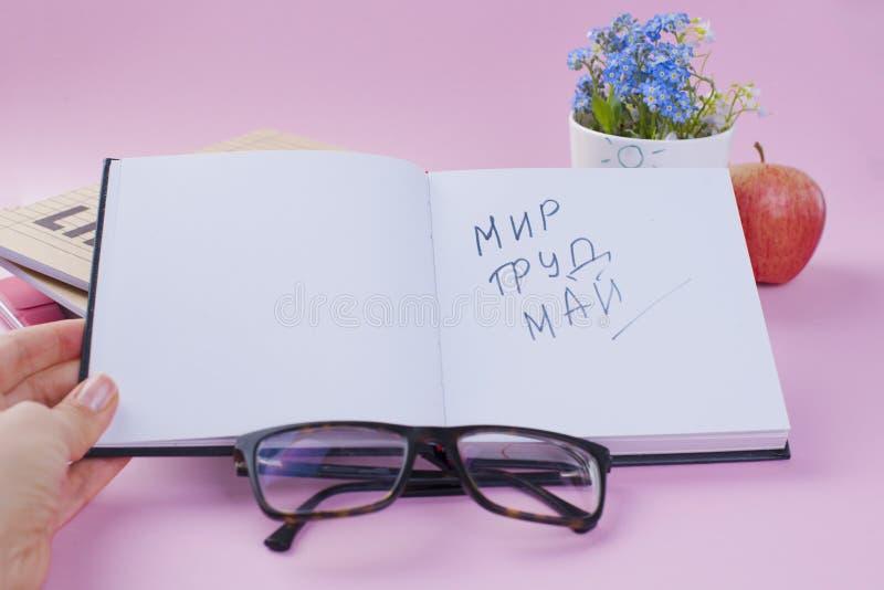 Μπλε λουλούδια και βιβλία και ένα μήλο Γυαλιά και ένα ανοικτό σημειωματάριο Εργασιακή ατμόσφαιρα Διακοπές της εργασίας το Μάιο κε στοκ εικόνες
