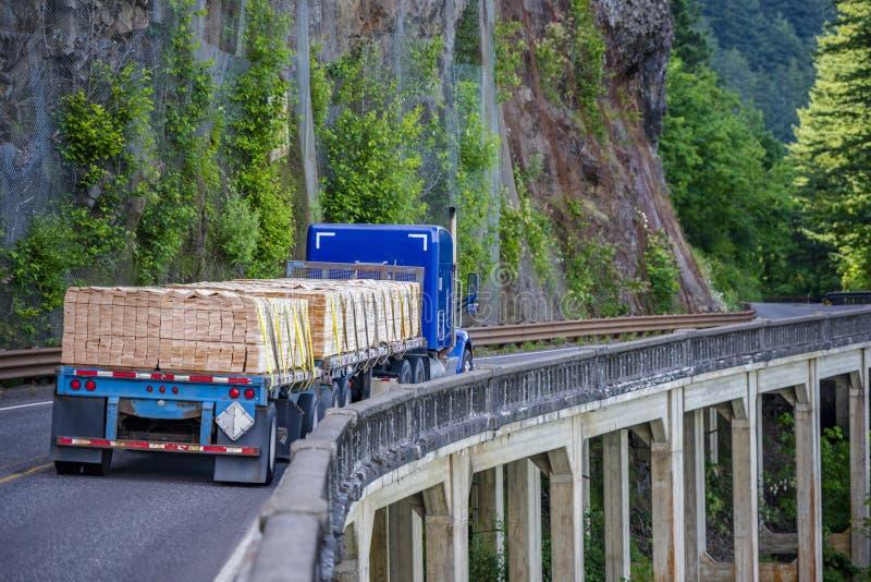 Μπλε μεγάλο κλασικό ημι φορτηγό εγκαταστάσεων γεώτρησης που μεταφέρει το ξύλο ξυλείας στην επίπεδη οδήγηση ρυμουλκών κρεβατιών ημ στοκ φωτογραφίες με δικαίωμα ελεύθερης χρήσης