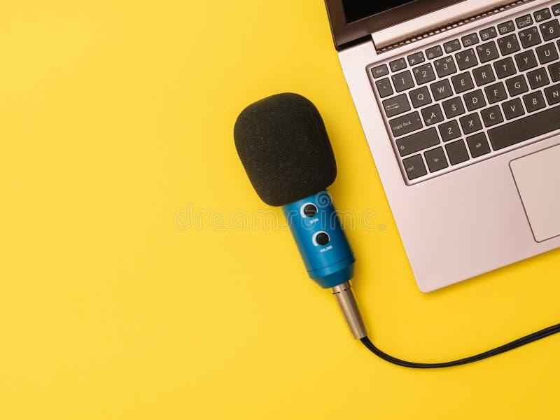 Μπλε μικρόφωνο και ένα lap-top στον κίτρινο πίνακα Η έννοια της οργάνωσης εργασιακών χώρων στοκ φωτογραφίες με δικαίωμα ελεύθερης χρήσης
