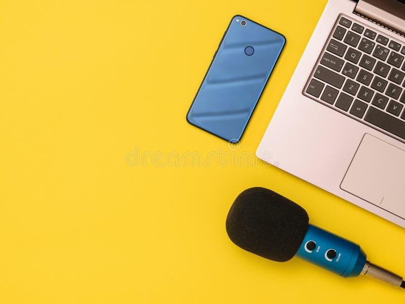 Μπλε μπλε μικρόφωνο smartphone και ένα lap-top στον κίτρινο πίνακα Η έννοια της οργάνωσης εργασιακών χώρων στοκ φωτογραφία με δικαίωμα ελεύθερης χρήσης