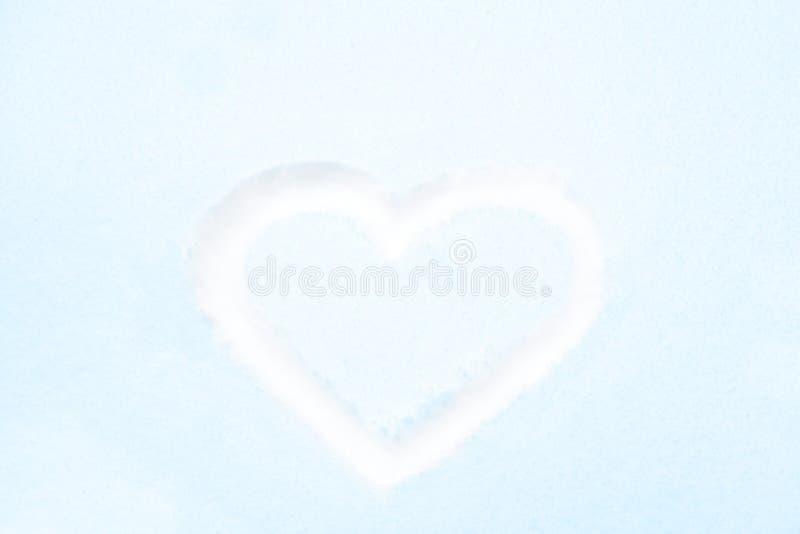 Μπλε μορφή καρδιών που επισύρει την προσοχή στο άσπρο χιόνι στοκ φωτογραφίες