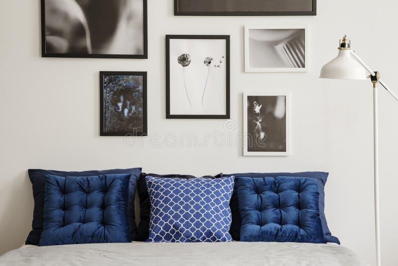 Μπλε ναυτικά μαξιλάρια στο κρεβάτι δίπλα στο λαμπτήρα στο άσπρο εσωτερικό κρεβατοκάμαρων με τη στοά των αφισών Πραγματική φωτογρα στοκ φωτογραφία