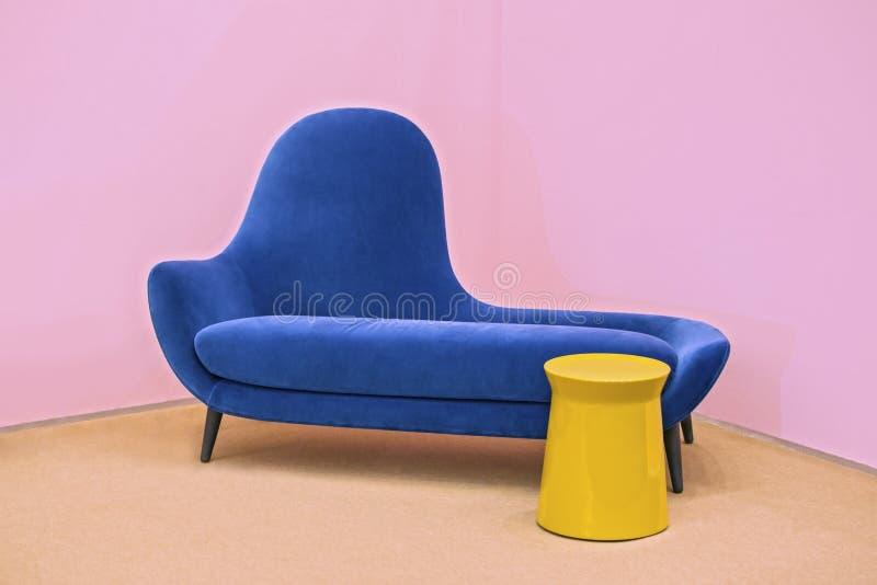 Μπλε ναυτικός καναπές σε ένα ρόδινο υπόβαθρο, λακωνικό εσωτερικό στοκ εικόνες