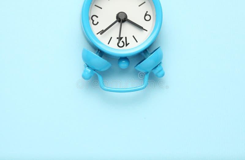 Μπλε ξυπνητήρι που απομονώνεται στο μπλε υπόβαθρο στοκ εικόνες