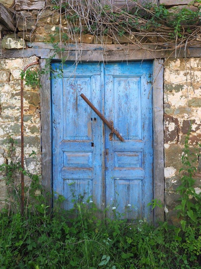 Μπλε ξύλινες πόρτες στο παλαιό πέτρινο ελληνικό του χωριού σπίτι στοκ φωτογραφίες