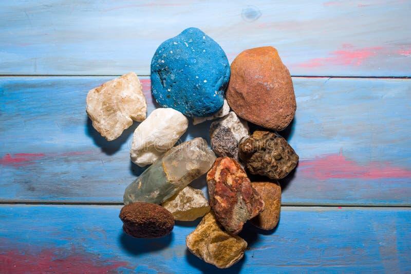 Μπλε ξύλινο υπόβαθρο με τις πέτρες των διαφορετικών χρωμάτων και των συστάσεων στοκ φωτογραφία με δικαίωμα ελεύθερης χρήσης