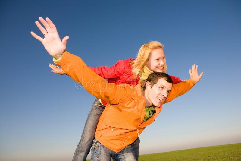 μπλε ουρανός αγάπης ζευγών που χαμογελά κάτω από τις νεολαίες στοκ εικόνες με δικαίωμα ελεύθερης χρήσης