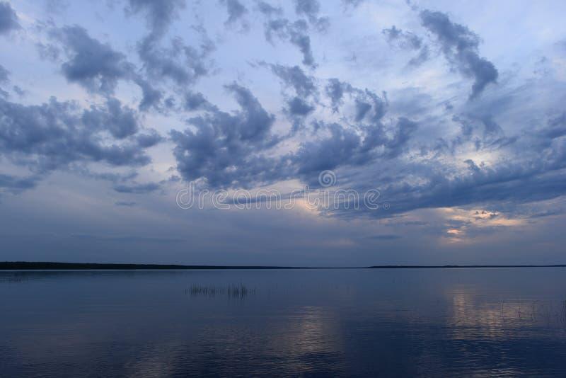 Μπλε ουρανός σατέν στο φως του ήλιου από τα σύννεφα με μια αντανάκλαση στο νερό της λίμνης στοκ εικόνες
