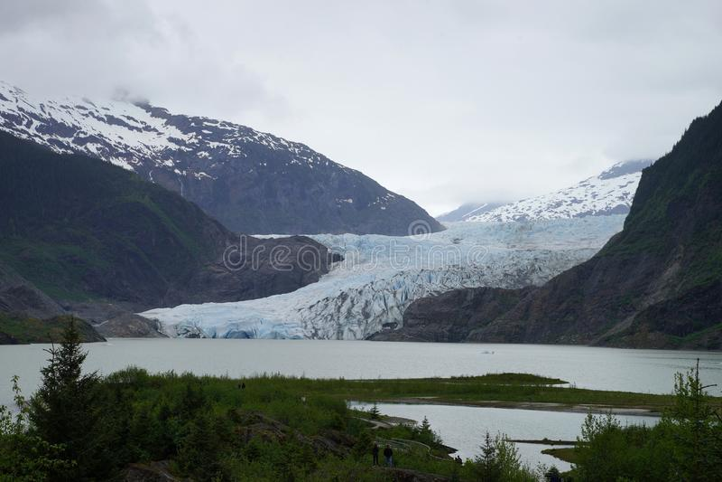 Μπλε πάγος του παγετώνα Mendenhall με τα χιονισμένα βουνά στο ίχνος υποβάθρου και πεζοπορίας στο πρώτο πλάνο στοκ εικόνες