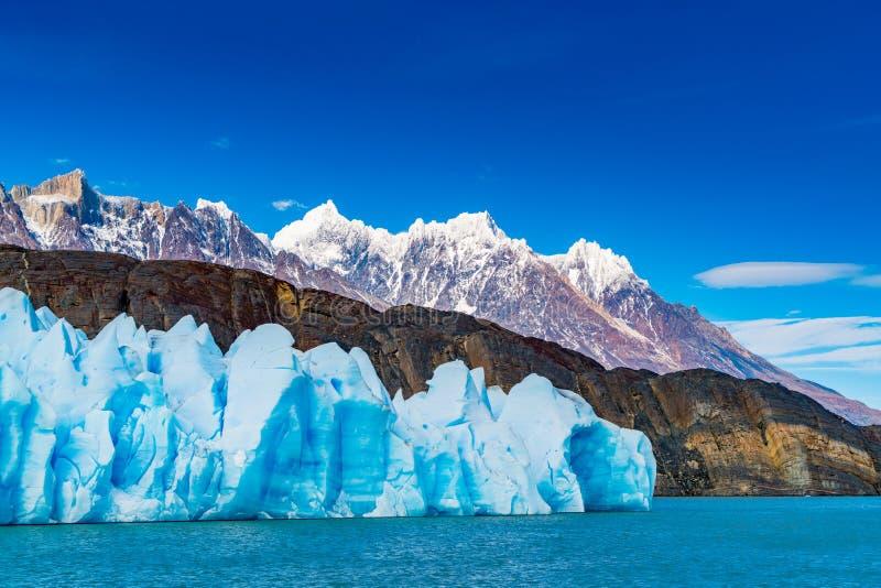 Μπλε παγόβουνο του γκρίζου παγετώνα, οι κυματισμοί της γκρίζας λίμνης και του όμορφου βουνού στοκ εικόνες με δικαίωμα ελεύθερης χρήσης