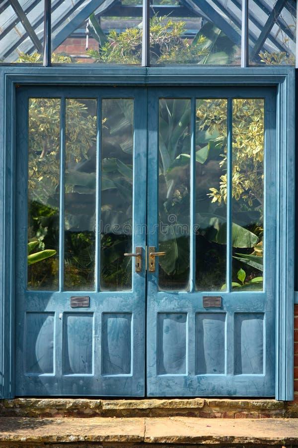 Μπλε παλαιές πόρτες στο τροπικό θερμοκήπιο στοκ φωτογραφίες