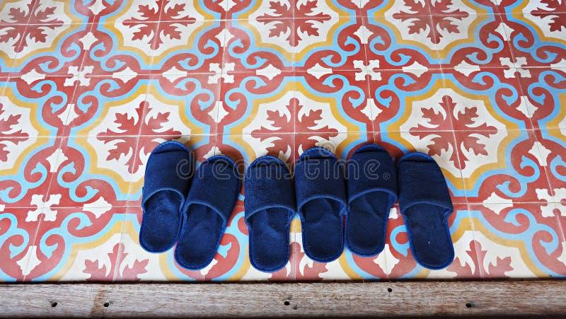 Μπλε παντόφλες στα εκλεκτής ποιότητας ασιατικά κεραμίδια πατωμάτων τέχνης στοκ φωτογραφία