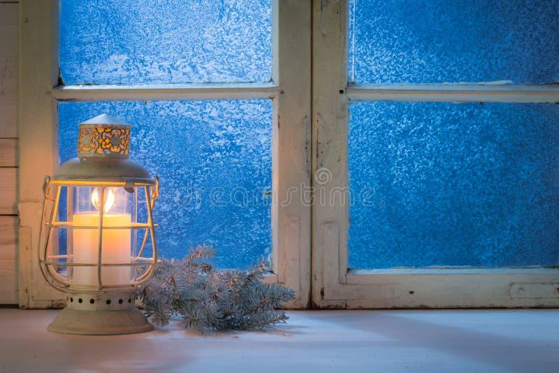 Μπλε παράθυρο τη νύχτα με το κάψιμο του κεριού για τα Χριστούγεννα στοκ φωτογραφία με δικαίωμα ελεύθερης χρήσης