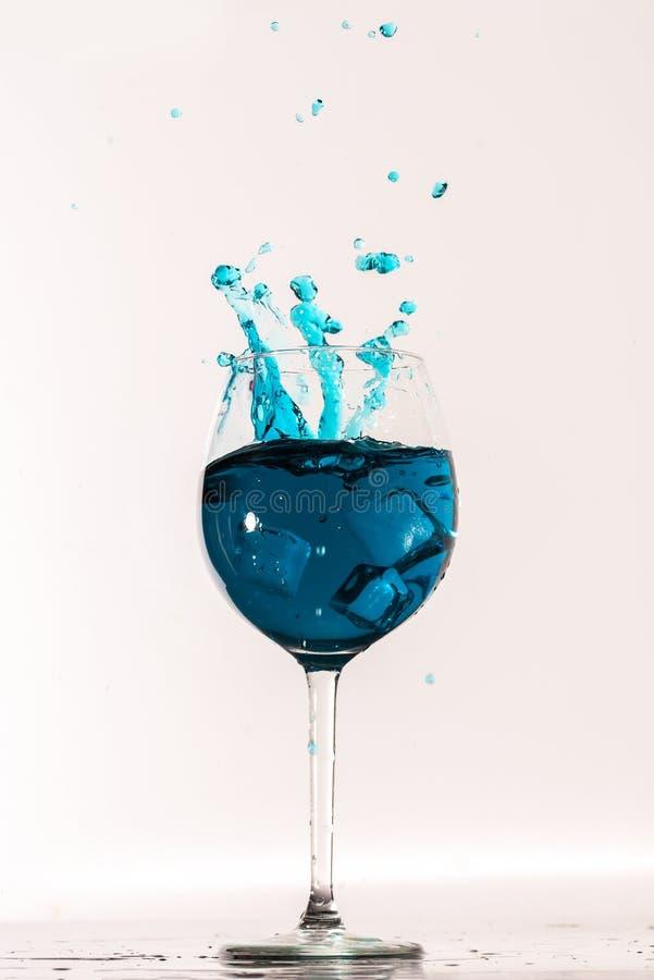 Μπλε παφλασμός ποτών με τους κύβους πάγου από το διαφανές γυαλί στοκ εικόνα με δικαίωμα ελεύθερης χρήσης