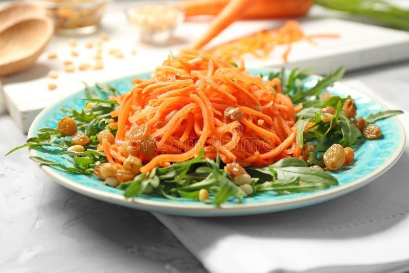 Μπλε πιάτο με την εύγευστη σαλάτα σταφίδων καρότων με το arugula στοκ εικόνες