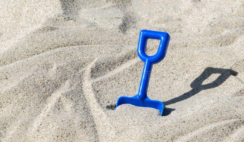 Μπλε πλαστικό φτυάρι σε μια αμμώδη παραλία μια ηλιόλουστη θερινή ημέρα στοκ φωτογραφία με δικαίωμα ελεύθερης χρήσης