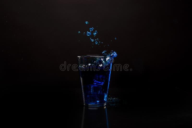 Μπλε ποτό γυαλιού που καταβρέχει έξω Πυροβοληθείς ενάντια στη μαύρη αντανακλαστική επιφάνεια στοκ φωτογραφία με δικαίωμα ελεύθερης χρήσης