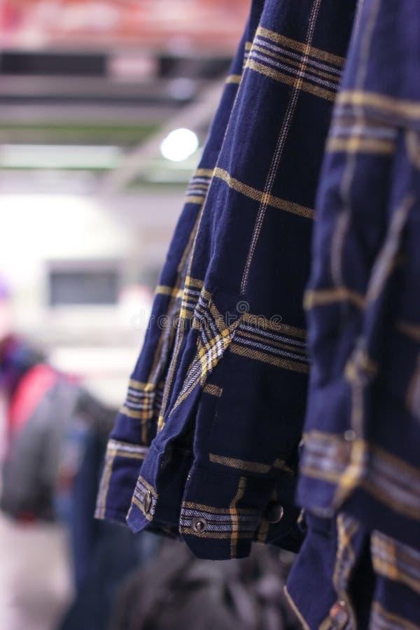 Μπλε πουκάμισα καρό ατόμων ` s στις κρεμάστρες στο κατάστημα στοκ εικόνες με δικαίωμα ελεύθερης χρήσης