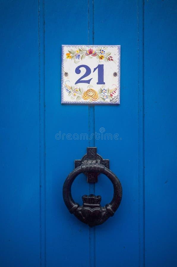 Μπλε πόρτες με το ψηφίο 21 και τα ρόπτρα στοκ εικόνες