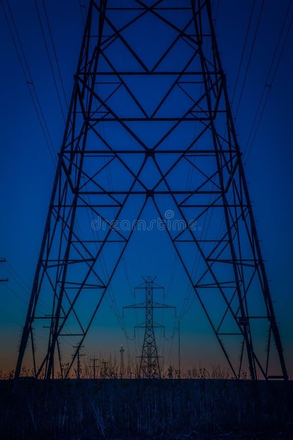 Μπλε πύργοι ηλεκτροφόρων καλωδίων ώρας στοκ εικόνα