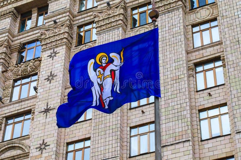 Μπλε σημαία Kyiv, η πρωτεύουσα της Ουκρανίας, με μια κάλυψη των όπλων στα πλαίσια του Κίεβου κτίριο γραφείων δημάρχου s, πόλη στοκ φωτογραφία