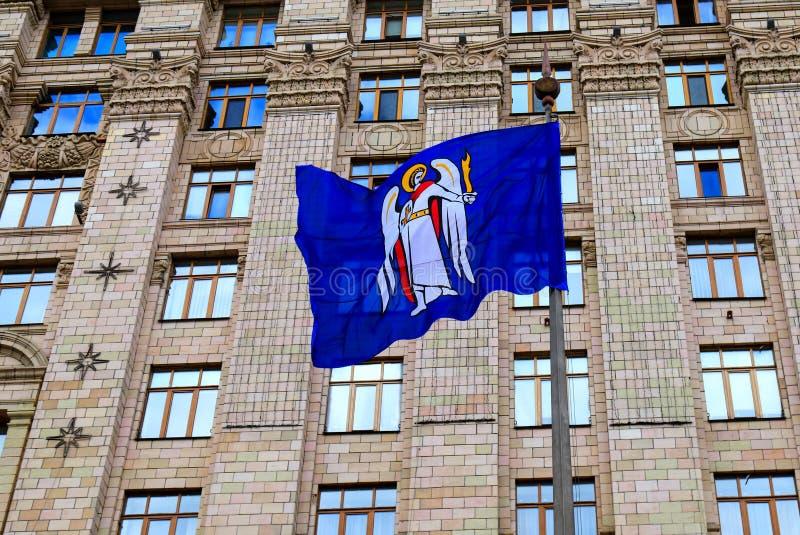 Μπλε σημαία Kyiv, η πρωτεύουσα της Ουκρανίας, με μια κάλυψη των όπλων στο υπόβαθρο του Κίεβου κτίριο γραφείων δημάρχου s, το συμβ στοκ φωτογραφία με δικαίωμα ελεύθερης χρήσης