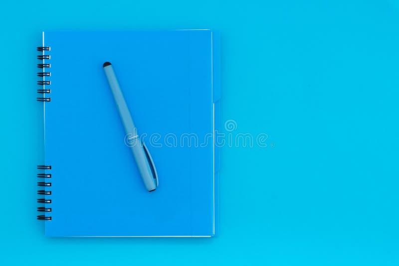 Μπλε σημειωματάριο με ένα μολύβι σε ένα μπλε υπόβαθρο Επίπεδος βάλτε το πρότυπο τοποθετήστε το κείμενο στοκ φωτογραφία με δικαίωμα ελεύθερης χρήσης