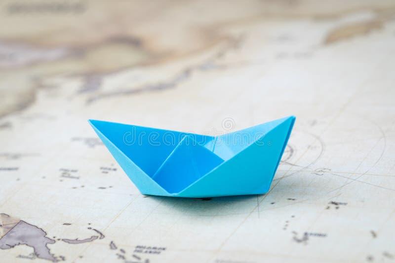 Μπλε σκάφος ή βάρκα εγγράφου origami στον εκλεκτής ποιότητας ωκεάνιο χάρτη με την τυπωμένη έννοια πυξίδων, ταξιδιού, πανιών ή κρο στοκ εικόνα