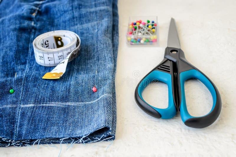 Μπλε σορτς τζιν, ρόλος της ταινίας ραφτών με τα εκατοστόμετρα και τις ίντσες, πολυ χρωματισμένες διευθυνμένες ράβοντας καρφίτσες  στοκ φωτογραφία