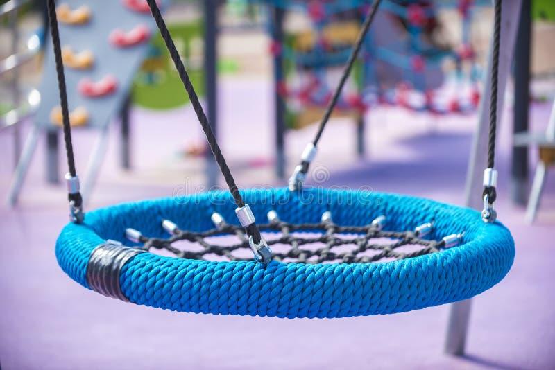 Μπλε στρογγυλή φωλιά τύπων ταλάντευσης στην παιδική χαρά Η έννοια της αθλητικής αναψυχής για τα παιδιά και τους εφήβους, μια ευτυ στοκ εικόνες με δικαίωμα ελεύθερης χρήσης