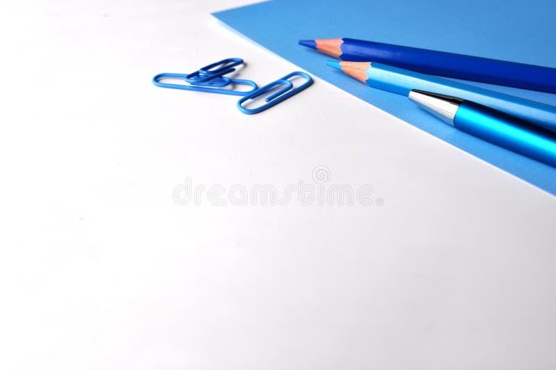 Μπλε στυλός και μολύβια, άσπρο και μπλε υπόβαθρο υπολογιστών γραφείου στοκ εικόνα
