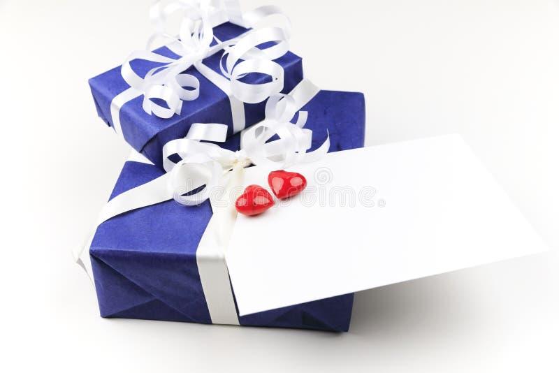 Μπλε συσκευασίες Χριστουγέννων με τις άσπρες κορδέλλες και μια επιστολή με δύο κόκκινες καρδιές στοκ εικόνα