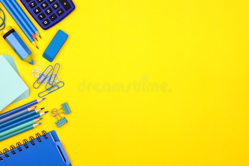 Μπλε σύνορα πλευράς σχολικών προμηθειών πέρα από ένα κίτρινο υπόβαθρο στοκ εικόνες με δικαίωμα ελεύθερης χρήσης