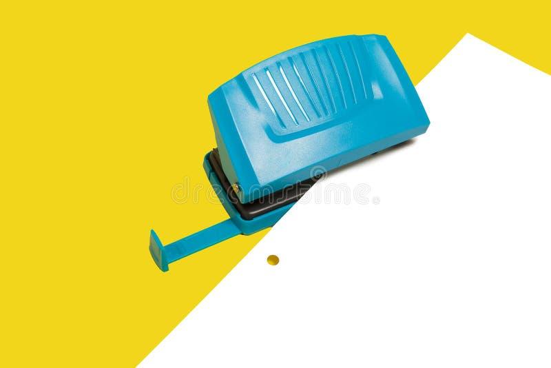 Μπλε τρύπα γραφείων puncher με ένα φύλλο του εγγράφου στοκ φωτογραφία με δικαίωμα ελεύθερης χρήσης