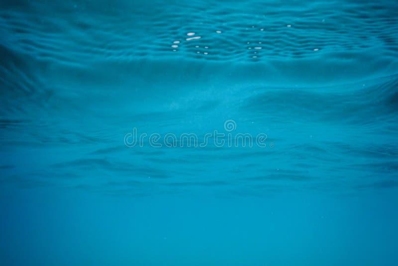 Μπλε υποβρύχια επιφάνεια και κυματισμοί, υποβρύχιο υπόβαθρο ακτίνων ήλιων στοκ εικόνα με δικαίωμα ελεύθερης χρήσης