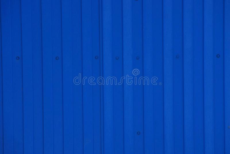 Μπλε υπόβαθρο μετάλλων από ένα τεμάχιο ενός παλαιού τοίχου στο φράκτη στοκ φωτογραφία με δικαίωμα ελεύθερης χρήσης