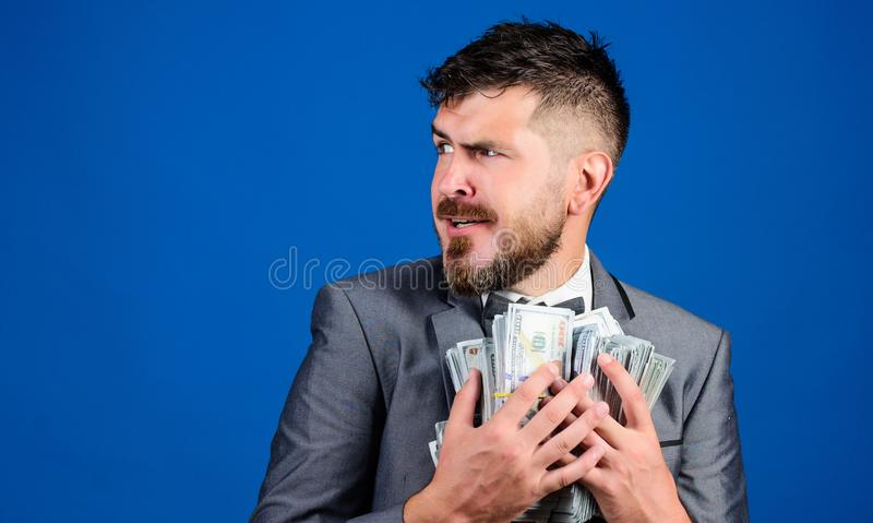 Μπλε υπόβαθρο χρημάτων σωρών λαβής επιχειρηματιών ατόμων γενειοφόρο Ο επιχειρηματίας έκπληκτος αισθάνεται όπως τον κλέφτη με το μ στοκ φωτογραφία με δικαίωμα ελεύθερης χρήσης