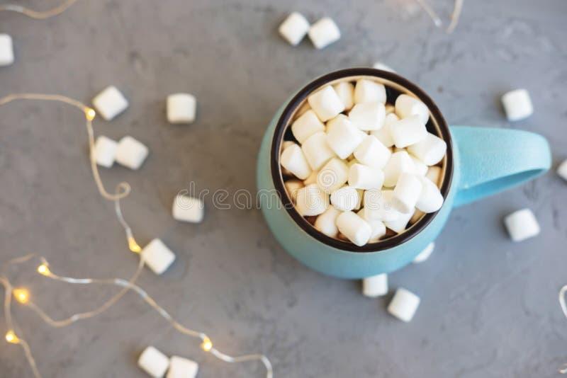 Μπλε φλιτζάνι του καφέ στο γκρίζο συγκεκριμένο υπόβαθρο με marshmallow και τη γιρλάντα Άνετες φθινόπωρο ποτών και χειμερινή έννοι στοκ εικόνες