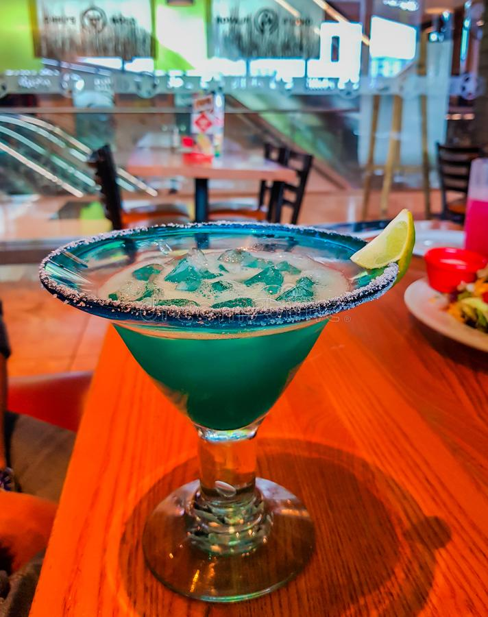 Μπλε χρωματισμένο μη αλκοολούχο ποτό με τον πάγο και το άλας και ζάχαρη στην άκρη με το λεμόνι στοκ εικόνα