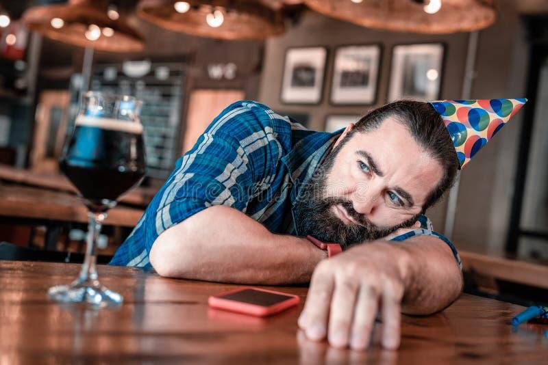 Μπλε-eyed άτομο που αισθάνεται απαθές περιμένοντας τους φιλοξενουμένους του στα γενέθλια στοκ φωτογραφίες
