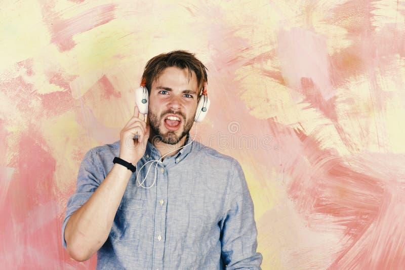 Μπλε eyed μοντέρνο hipster με το smartphone Μουσικός τρόπος ζωής Εύθυμα εφηβικά τραγούδια ακούσματος του DJ μέσω των ακουστικών στοκ φωτογραφίες με δικαίωμα ελεύθερης χρήσης