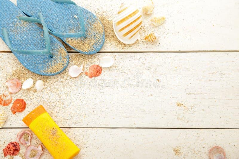 Μπλε flipflops, sunblock, και θαλασσινά κοχύλια στον άσπρο ξύλινο πίνακα στοκ εικόνα