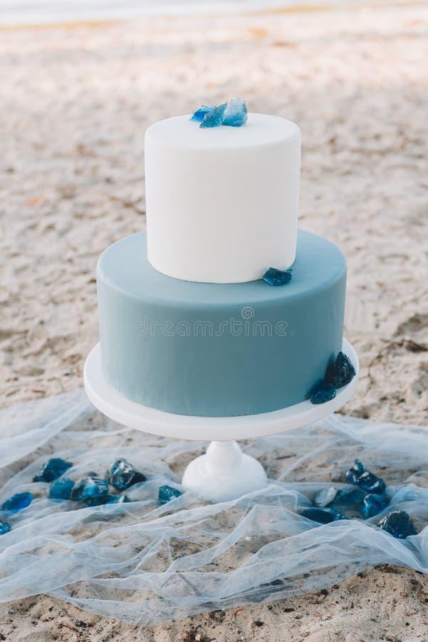 Μπλε two-tiered γαμήλιο κέικ με σε μια παραλία στοκ φωτογραφίες με δικαίωμα ελεύθερης χρήσης