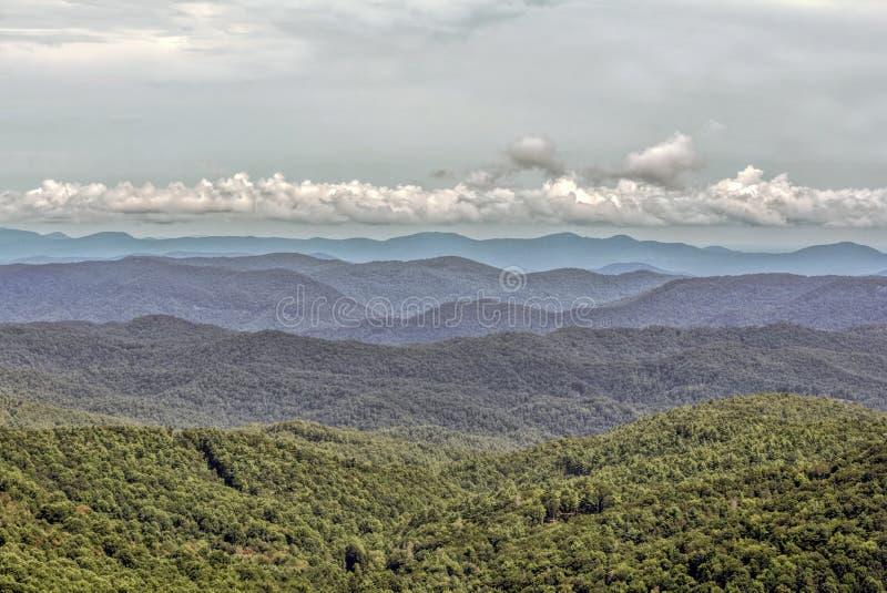 Μπλε vista βουνών κορυφογραμμών στο φυσώντας βράχο στοκ φωτογραφία