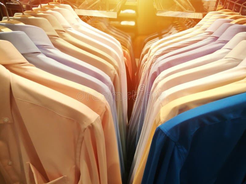 Μπλούζες με διαφορετικά χρώματα σε κρεμάστρες σε κατάστημα ειδών ρουχισμού στοκ εικόνες με δικαίωμα ελεύθερης χρήσης