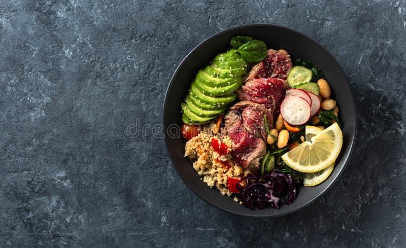 Μπολ με υγιεινό φαγητό βουδιστικό με μπριζόλα, φασόλια, κουσκούς, αβοκάντο και λαχανικά σκούρο φόντο με αντιγραφή στοκ εικόνα με δικαίωμα ελεύθερης χρήσης
