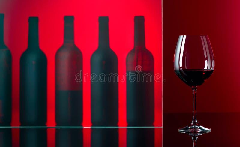 Μπουκάλια και ποτήρι του κόκκινου κρασιού σε ένα κόκκινο υπόβαθρο στοκ φωτογραφίες με δικαίωμα ελεύθερης χρήσης